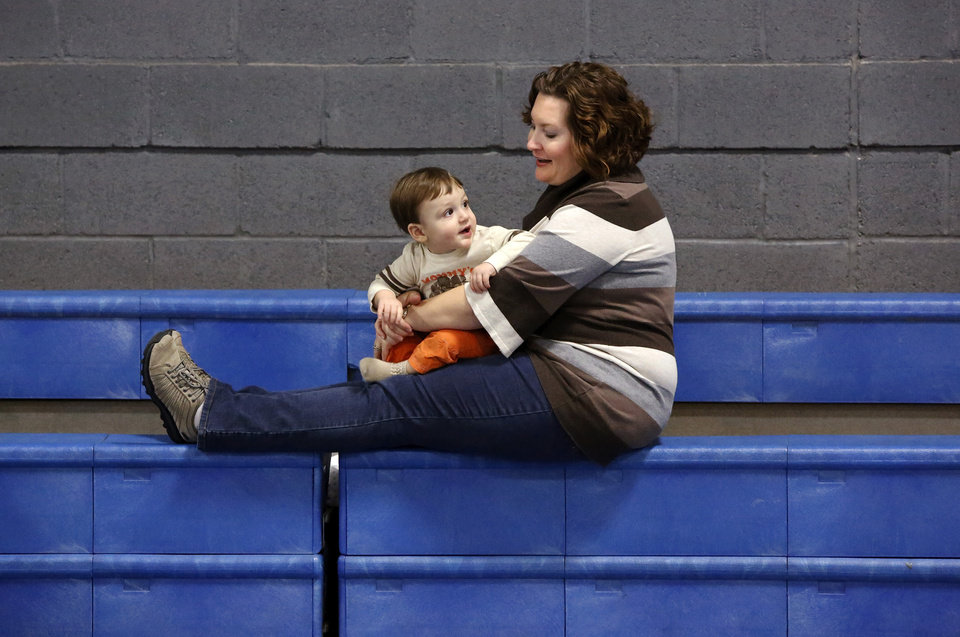 Amber Meiki waits on bleachers with her son, Shiloh, 11 months, to hear the decision of the judges. It was worth waiting as Shiloh's time of 15.4 seconds took top honors. Diaper Dash / Baby Crawl contest  at Jackie Cooper Gym in Yukon, Saturday, Jan. 5, 2013.  Organizers said nine entries registered to compete in the three categories. Age divisions were six to nine months old; 10 to14 months-old; and walking toddlers. Winner in the youngest category was Liam Sorrels, eight months. Winner of the middle category was Shiloh Meiki, 11 months, and the lone entrant in the walking toddler category was Cooper Ferrell, i year old. The contestants raced individually and were timed by judges. The babies were required to crawl  from one end to the other on a 20 foot mat. Quickest time was awarded first place.   Photo by Jim Beckel, The Oklahoman