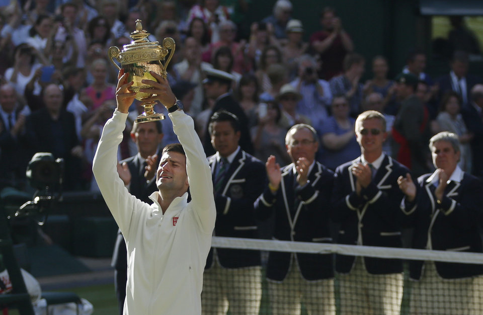 Photo - Novak Djokovic of Serbia holds the trophy after defeating Roger Federer of Switzerland in the men's singles final at the All England Lawn Tennis Championships in Wimbledon, London, Sunday July 6, 2014. (AP Photo/Pavel Golovkin)