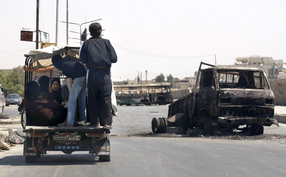 Photo -   A Syrian family on the back of a truck pass a burned military vehicle on a street in the town of Hanano in Aleppo, Syria, Friday, Aug. 17, 2012. Rebel footholds in Aleppo have been the target of weeks of Syrian shelling and air attacks as part of wider offensives by President Bashar Assad's regime. Rebels have been driven from some areas, but the report of clashes near the airport suggests the battles could be shifting to new fronts. (AP Photo/ Khalil Hamra)