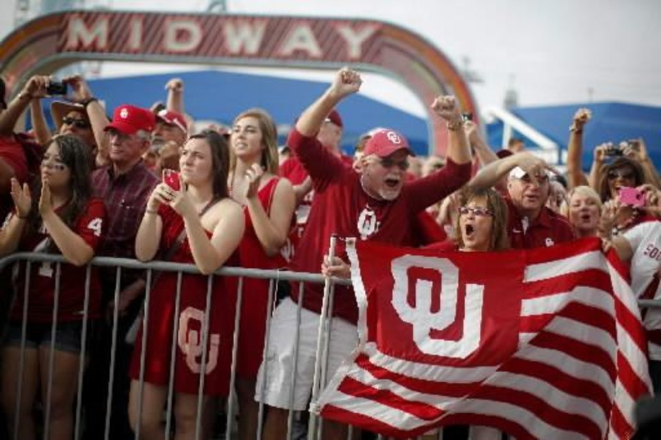 Photo - Oklahoma fans greet the team before the Red River Rivalry college football game between the University of Oklahoma and the University of Texas at the Cotton Bowl in Dallas, Saturday, Oct. 13, 2012. Photo by Bryan Terry