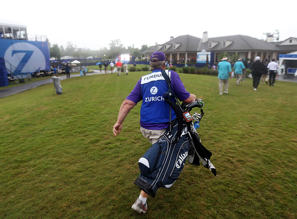 A caddy makes his way to the brick clubhouse as officials order the evacuation of all temporary structures following a tornado warning during the Zurich Classic pro-am golf tournament at the TPC Louisiana on Wednesday, April 24 , 2013 in Avondale, La.  (AP Photo/Nola.com, Michael DeMocker)