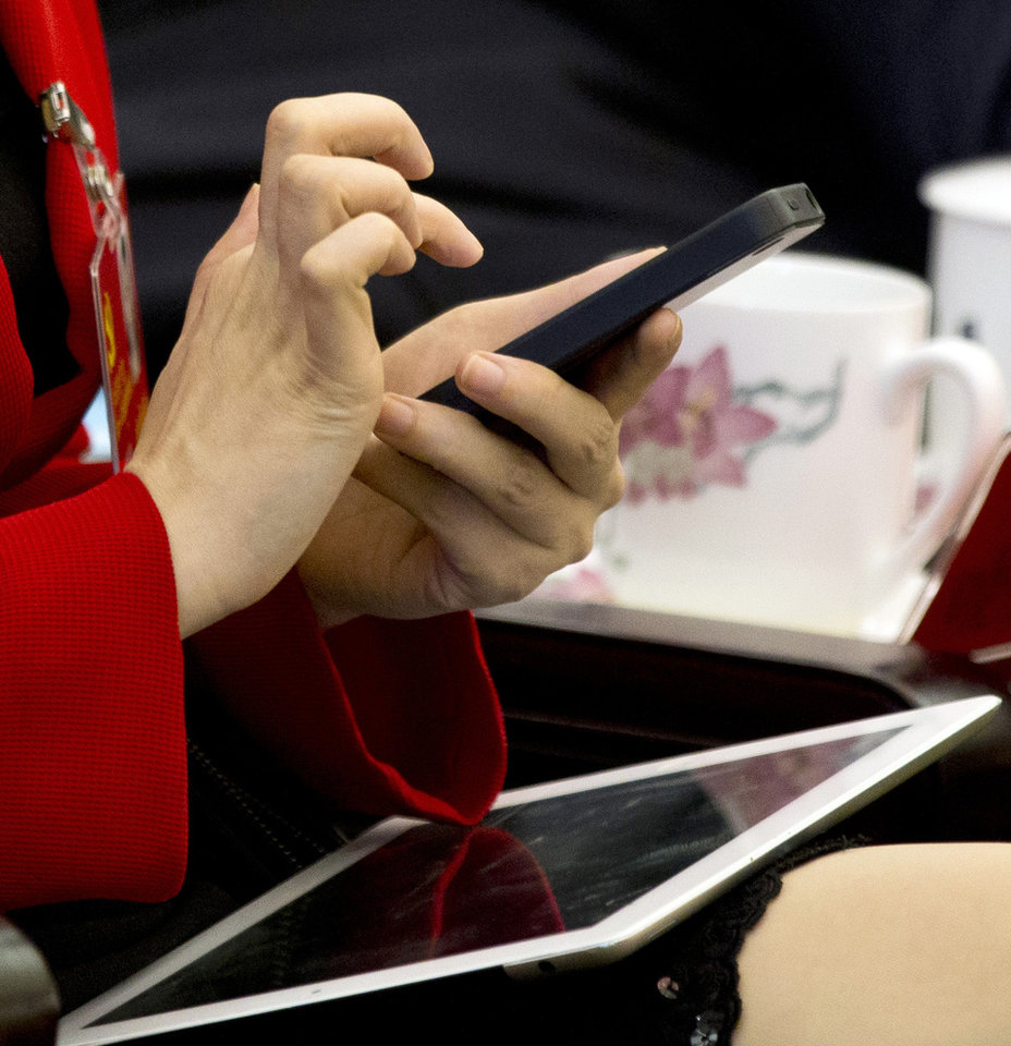 In this Nov. 9, 2012 photo, a Communist Party delegate uses her iPhone with an iPad resting on her legs during a group discussion meeting as part of the 18th Communist Party Congress at the Great Hall of the People in Beijing, China. During China's last party congress, the cadres in charge of the world's most populous nation didn't know a hashtag from a hyperlink. But five years on, there's a new message from Beijing: The political transition will be microblogged. (AP Photo/Alexander F. Yuan)