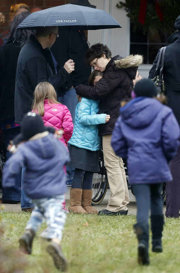 Photo - A woman embraces a child as children run outside of St. Rose of Lima Roman Catholic Church before a Sunday mass service, Sunday, Dec. 16, 2012, in Newtown, Conn. On Friday, a gunman allegedly killed his mother at their home and then opened fire inside the Sandy Hook Elementary School in Newtown, killing 26 people, including 20 children. (AP Photo/Julio Cortez)