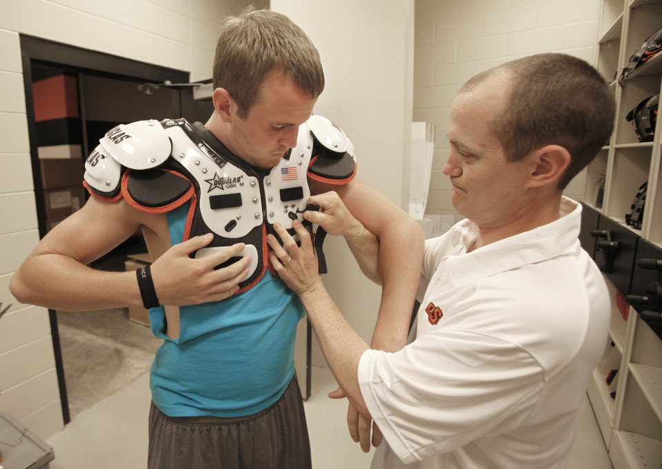 Photo - OKLAHOMA STATE UNIVERSITY / OSU / COLLEGE FOOTBALL / EQUIPMENT COORDINATOR: Nathan Sorenson is fitted for shoulder pads by Wes Edwards in The Oklahoma State equipment room in Boone Pickens Stadium in Stillwater, Oklahoma July 28 , 2010. Photo by Steve Gooch, The Oklahoman ORG XMIT: KOD