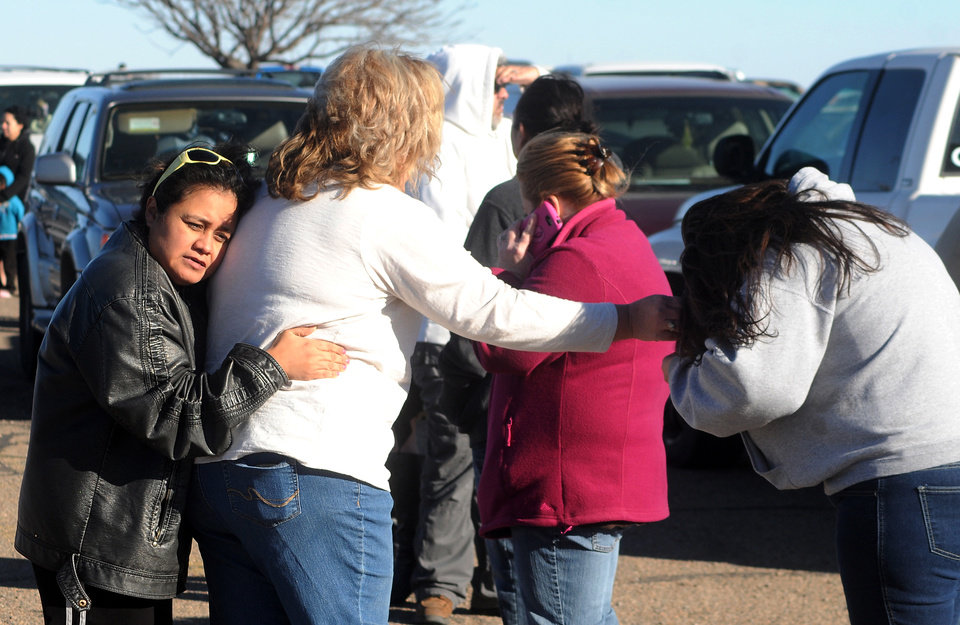 Photo - People wait for news at a staging ground area set up at the Roswell Mall after a shooting at Berrendo Middle School, Tuesday, Jan. 14, 2014, in Roswell, N.M. A shooter opened fire at the middle school, injuring at least two students before being taken into custody. Roswell police said the school was placed on lockdown, and the suspected shooter was arrested. (AP Photo/Roswell Daily Record, Mark Wilson)