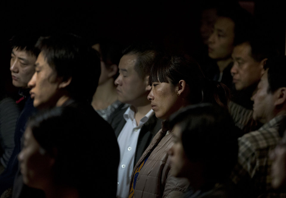 Photo - Relatives of Chinese passengers aboard the missing Malaysia Airlines Flight MH370 watch a TV news program about the plane as they wait for a news briefing held by the airlines' officials at a hotel ballroom in Beijing Monday, March 17, 2014. The search for the missing Malaysian jet pushed deep into the northern and southern hemispheres Monday as Australia took the lead in scouring the seas of the southern Indian Ocean and Kazakhstan - about 10,000 miles to the northwest - answered Malaysia's call for help in the unprecedented hunt. (AP Photo/Andy Wong)
