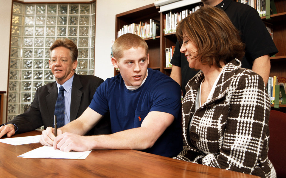 Photo - Norman North's Brenden Brown, with parents Dale and Christine, signs a letter of intent Wednesday. Photo by Steve Sisney, The Oklahoman