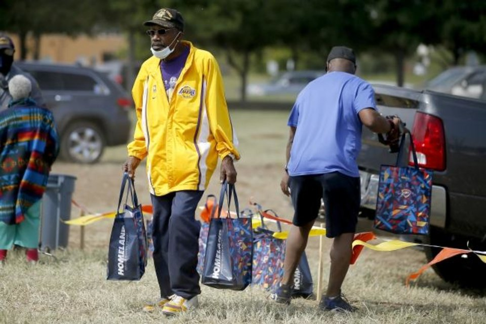 Photo -  McKinley Brown carries gift bags as he leaves the groundbreaking for a new Homeland grocery store at the corner of NE 36 and Lincoln Boulevard in Oklahoma City Thursday.  [Bryan Terry/The Oklahoman]