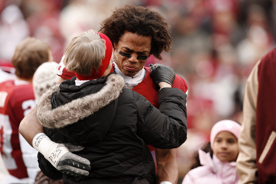 Photo - Senior Lewis Baker (16) gives an emotional hug to friends and family members during senior introductions before the college football game between the University of Oklahoma Sooners (OU) and the Oklahoma State University Cowboys (OSU) at the Gaylord Family-Memorial Stadium on Saturday, Nov. 24, 2007, in Norman, Okla. 