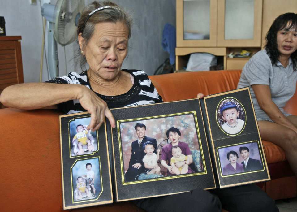 Photo - Suwarni the mother of Sugianto Lo, who was onboard the Malaysia Airlines plane MH370 with his wife Vinny, shows her son's family portraits at her residence in Medan, North Sumatra, Indonesia, Tuesday, March 25, 2014. After 17 days of desperation and doubt over the missing Malaysia Airlines jet, the country's officials said an analysis of satellite data points to a