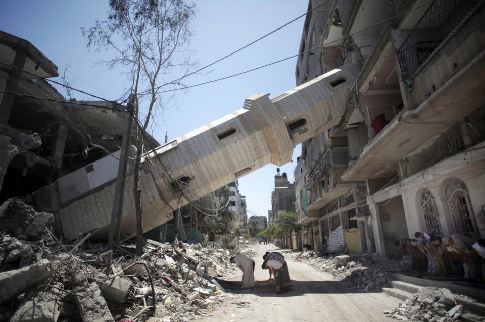 Photo - Palestinians attend Friday noon prayers in the shadow of a toppled minaret at a mosque that was hit by Israeli strikes, in Gaza City, Friday, Aug. 8, 2014, as Israel and Gaza militants resumed cross-border attacks after a three-day truce expired and Egyptian-brokered talks on a new border deal for blockaded Gaza hit a deadlock. (AP Photo/Khalil Hamra)