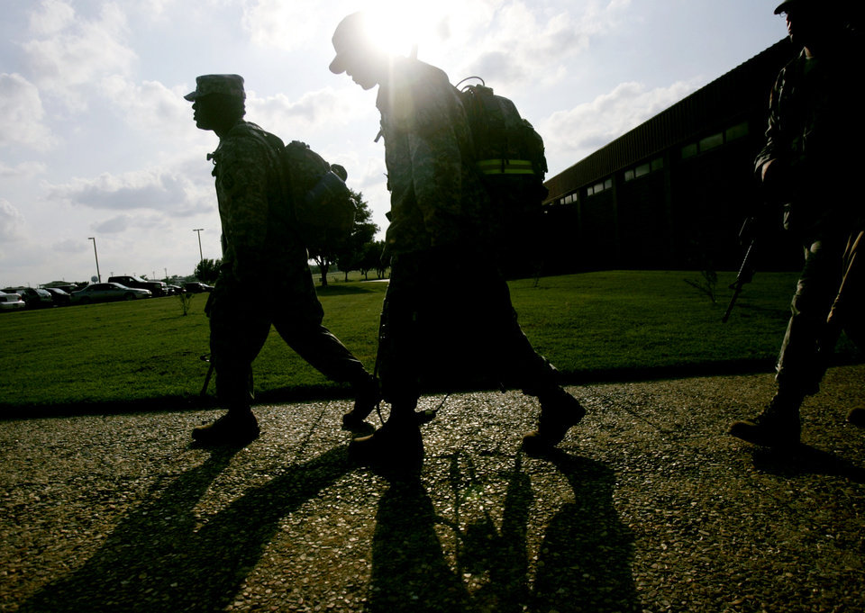 Photo - IRAQ WAR, MILITARY, ARMY, DEPLOY, DEPLOYMENT, FORT SILL: Sgt. 1st Class Kenric Brooks (left) joins other soldiers as they walk toward buses that will take them to the Lawton Airport to deploy to Iraq on July 12, 2007. By John Clanton, The Oklahoman ORG XMIT: KOD