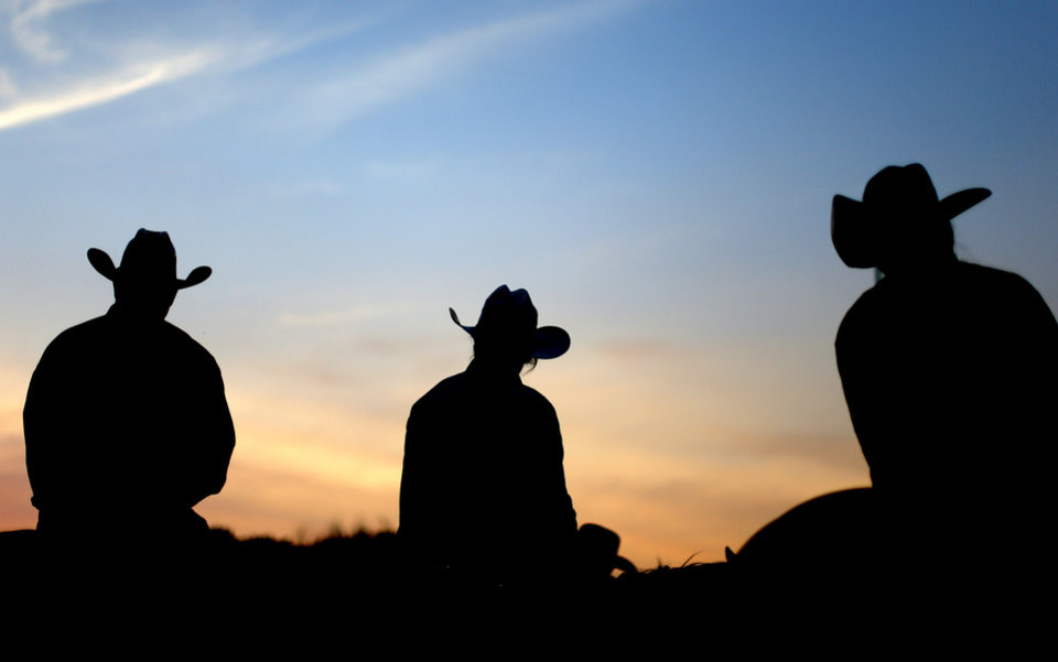 Contestants and rodeo workers watch the annual LibertyFest Rodeo as the sun sets in Edmond. PHOTO BY BRYAN TERRY, THE OKLAHOMAN. Bryan Terry - THE OKLAHOMAN