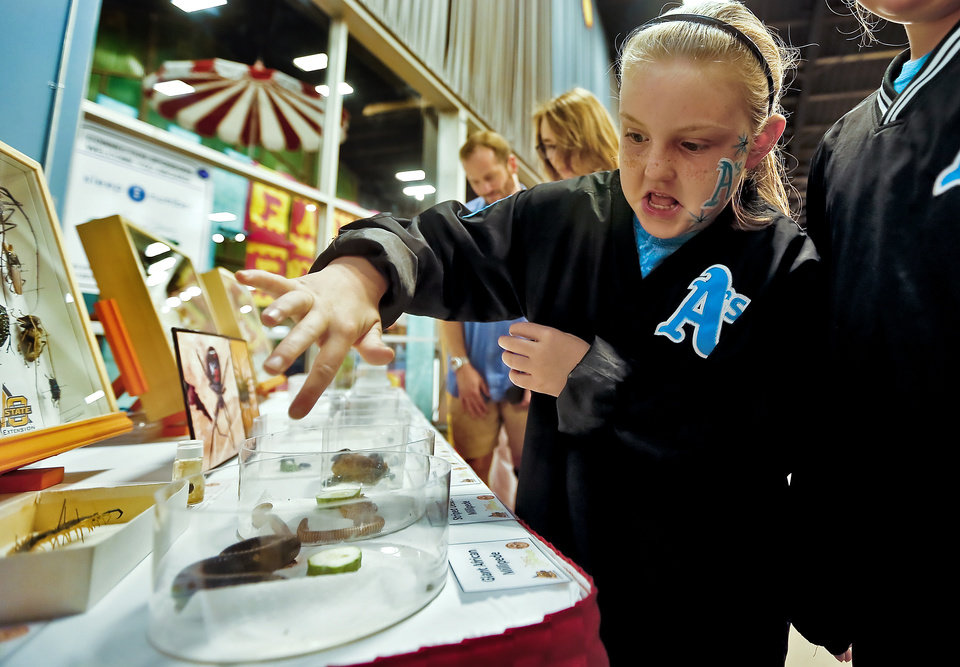 Parker Norvell reacts as she touches the giant African Millipede on display at the Oklahoma State University bug display in the AGtropolis building at the 2013 Oklahoma State Fair on Friday, Sept. 20, 2013 in Oklahoma City, Okla. Photo by Chris Landsberger, The Oklahoman