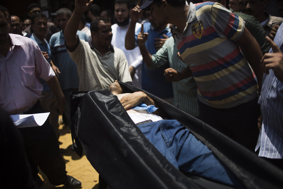 Photo - The corpse of a supporter for Egypt's ousted President Mohammed Morsi is brought to a morgue in Cairo, Egypt, Monday, July 8, 2013. Egyptian soldiers and police opened fire on supporters of the ousted president early Monday in violence that left dozens of people killed, including one officer, outside a military building in Cairo where demonstrators had been holding a sit-in, government officials and witnesses said. (AP Photo/Manu Brabo)