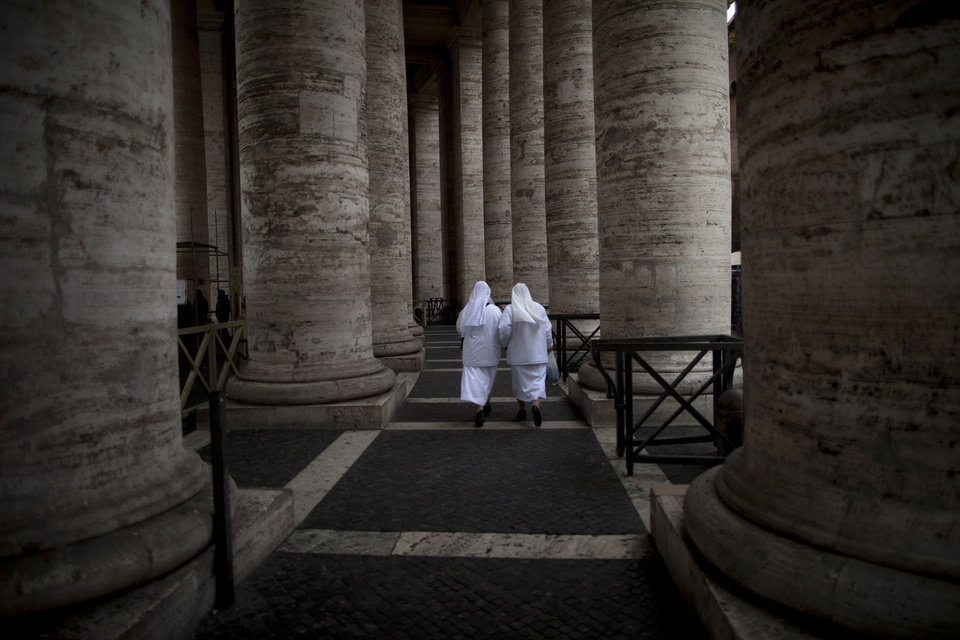 Photo - Two nuns walk under the Bernini colonnade in St. Peter's Square at the Vatican, Monday, Feb. 25, 2013. Pope Benedict XVI has changed the rules of the conclave that will elect his successor, allowing cardinals to move up the start date if all of them arrive in Rome before the usual 15-day transition between pontificates. Benedict signed a legal document, issued Monday, with some line-by-line changes to the 1996 Vatican law governing the election of a new pope. It is one of his last acts as pope before resigning Thursday. (AP Photo/Oded Balilty)