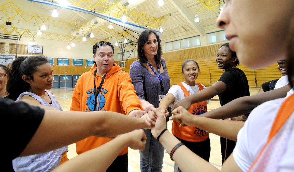 Gabrielle Ludwig, a 6-foot-6-inch transsexual player on Mission College's women's basketball squad, joins teammates during practice on Friday, Dec. 7, 2012, in Santa Clara, Calif. At left is team coach Corey Cafferata. Gabrielle Ludwig made sports history this month as a basketball player at a Northern California community college. The 50-year-old transsexual, Army veteran, father and Mission College freshman is believed to be the first hoopster to play college ball as both a man and a woman. (AP Photo/Noah Berger)