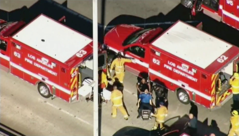 Photo - In this video frame grab provided by KTTV Los Angeles, emergency workers prepare to transfer a wounded Transportation Security Administration officer to a waiting ambulance after a shooting in Terminal 3 at Los Angeles International Airport on Friday, Nov. 1, 2013. A man pulled a semi-automatic rifle from a bag and shot his way past a security checkpoint at the airport on Friday, killing a TSA officer and wounding at least three others, authorities said. (AP Photo/KTTV)  MANDATORY CREDIT