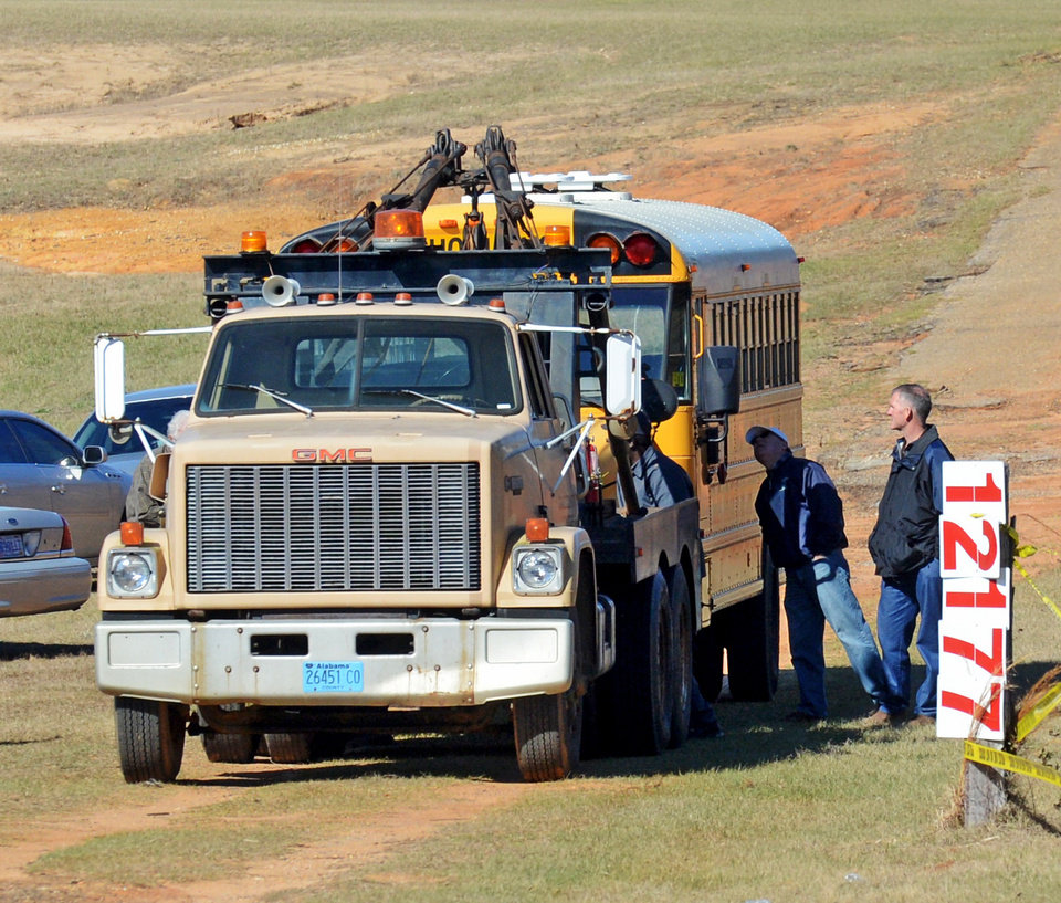 Photo - Law enforcement officials remove the bus Friday, Feb. 1, 2013, that Charles Poland was driving when he was fatally shot in Midland City, Ala. Suspect Jimmy Lee Dykes has been holed up in a bunker on his property with the 5-year-old child he took from the bus since the late afternoon shooting on Tuesday, Jan. 29. (AP Photo/al.com, Julie Bennett)