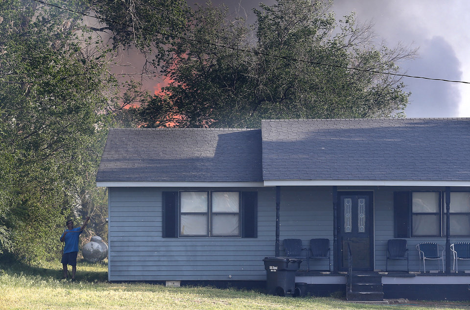 Photo - Tom Humes sprays water on a home as a wildfire burns in the back near East Seward Road and Oak Hill Road,  Sunday, May 4, 2014. Photo by Sarah Phipps, The Oklahoman