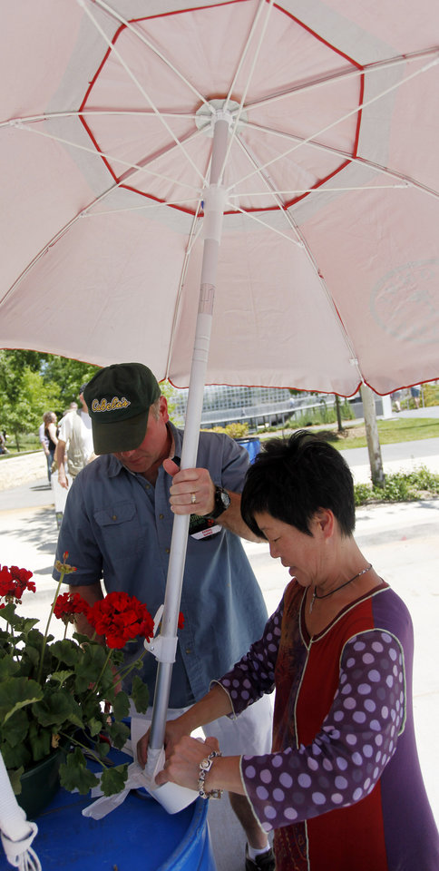 Photo - Artist Randal Napier, left, helps fellow artist MiKyung Cunningham secure her umbrella during opening day of the Festival of the Arts in downtown Oklahoma City TUesday, April 24, 2012. Photo by Doug Hoke, The Oklahoman