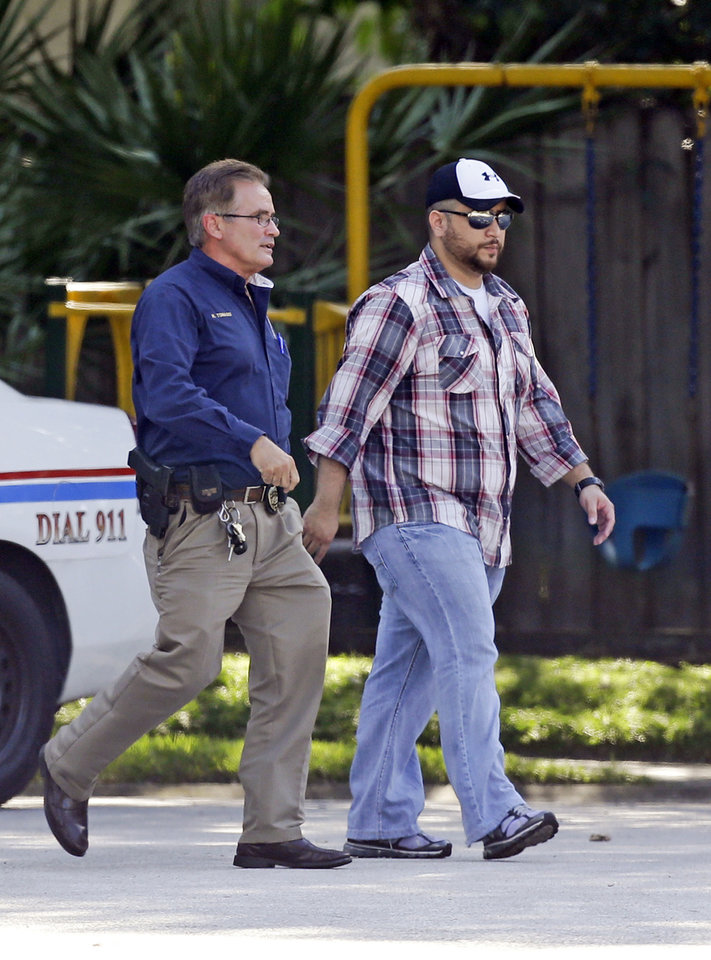 Photo - George Zimmerman, right, is escorted to a home by a Lake Mary police officer, Monday, Sept. 9, 2013, in Lake Mary, Fla., after a domestic incident in the neighborhood where Zimmerman and his wife Shellie had lived during his murder trial. Zimmerman's wife says on a 911 call that her estranged husband punched her father in the nose, grabbed an iPad out of her hand and smashed it and threatened them both with a gun. Zimmerman was recently found not guilty for the 2012 shooting death of Trayvon Martin. (AP Photo/John Raoux)