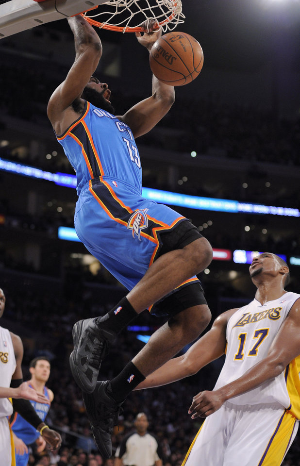 Photo - Oklahoma City Thunder guard James Harden, left, dunks as Los Angeles Lakers center Andrew Bynum looks on during the first half of an NBA basketball game Sunday, April 10, 2011, in Los Angeles. (AP Photo/Mark J. Terrill)