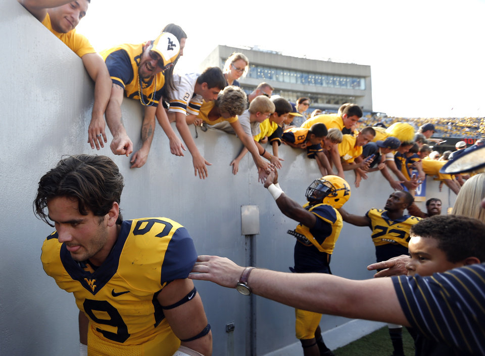 Photo - Clint Trickett (9) runs off the field after celebrating with fans following a college football game between the Oklahoma State University and West Virginia University on Mountaineer Field at Milan Puskar Stadium in Morgantown, W. Va.,   Saturday, Sept. 28, 2013. Photo by Sarah Phipps, The Oklahoman