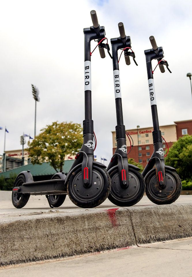 Photo - Bird Scooters are parked along the a Bricktown sidewalk in downtown Oklahoma City, Okla. on Tuesday, Aug. 14, 2018.  The city council will consider cracking down on electric rental scooters parked in the public right of way. Photo by Chris Landsberger, The Oklahoman