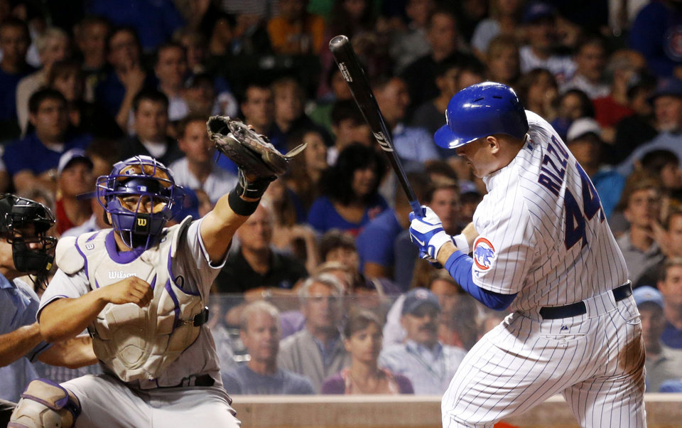 Photo - Chicago Cubs' Anthony Rizzo, right, dodges a high pitch from Colorado Rockies starting pitcher Jorge De La Rosa and caught by catcher Wilin Rosario, during the fourth inning of a baseball game Tuesday, July 29, 2014, in Chicago. (AP Photo/Charles Rex Arbogast)