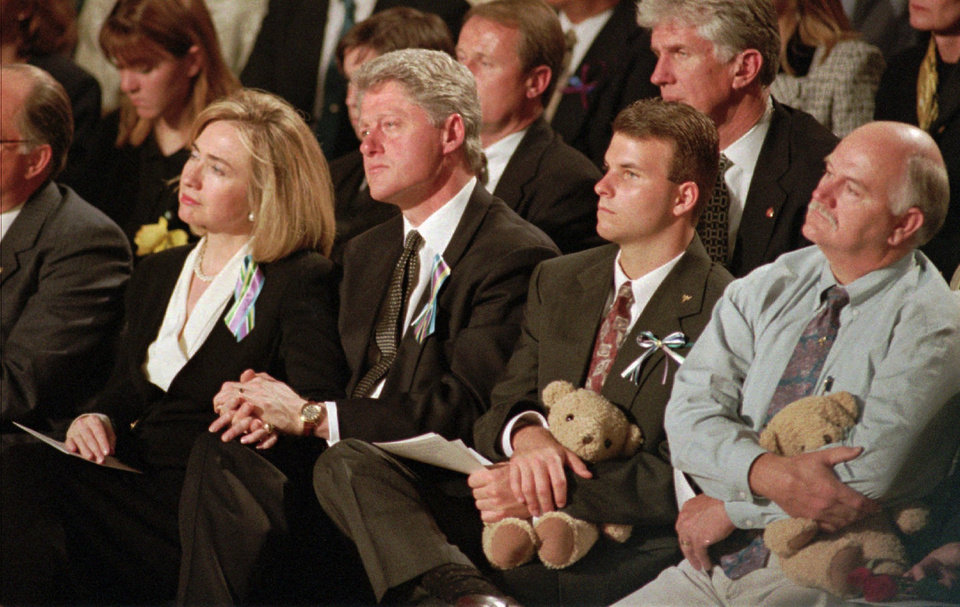 Photo - First lady Hillary Rodham Clinton, left, holds hands with President Clinton during a prayer service, at the Oklahoma State Fair Arena,  in Oklahoma City, Sunday, April 23, 1995, to remember the victims of Wednesday's deadly car bombing in Oklahoma City.  The men at right are unidentified. (AP Photo/Beth A. Keiser)