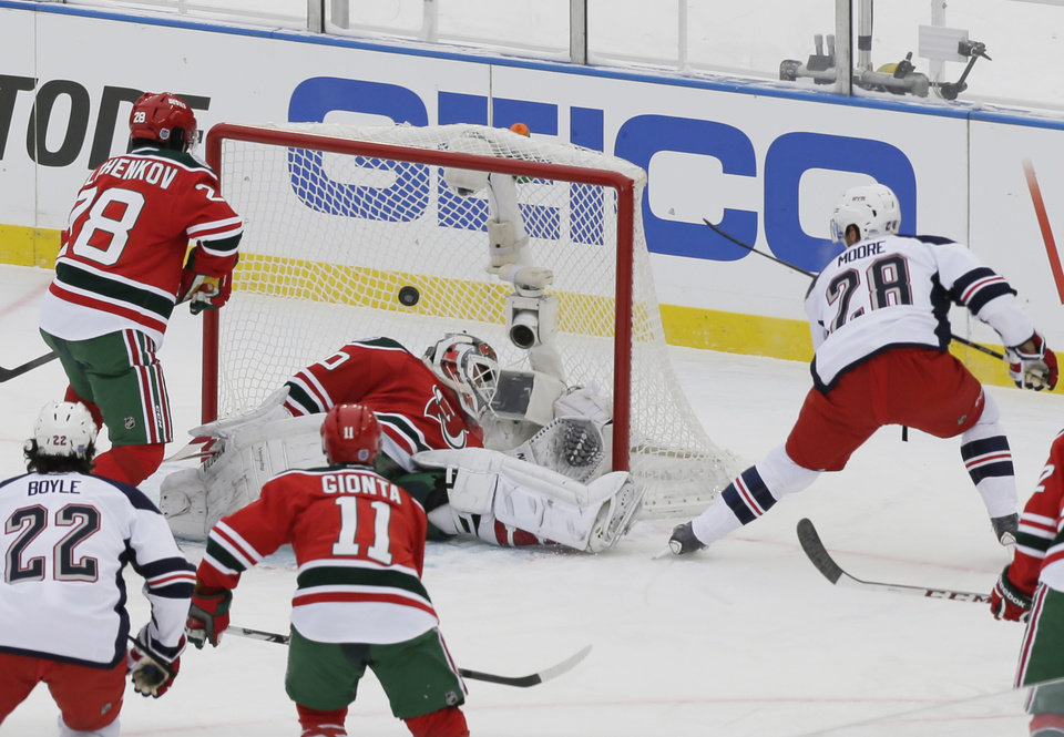 Photo - New York Rangers' Dominic Moore (28) shoots the puck past New Jersey Devils goalie Martin Brodeur (30) during the first period of an outdoor NHL hockey game Sunday, Jan. 26, 2014, at Yankee Stadium in New York. (AP Photo/Frank Franklin II)