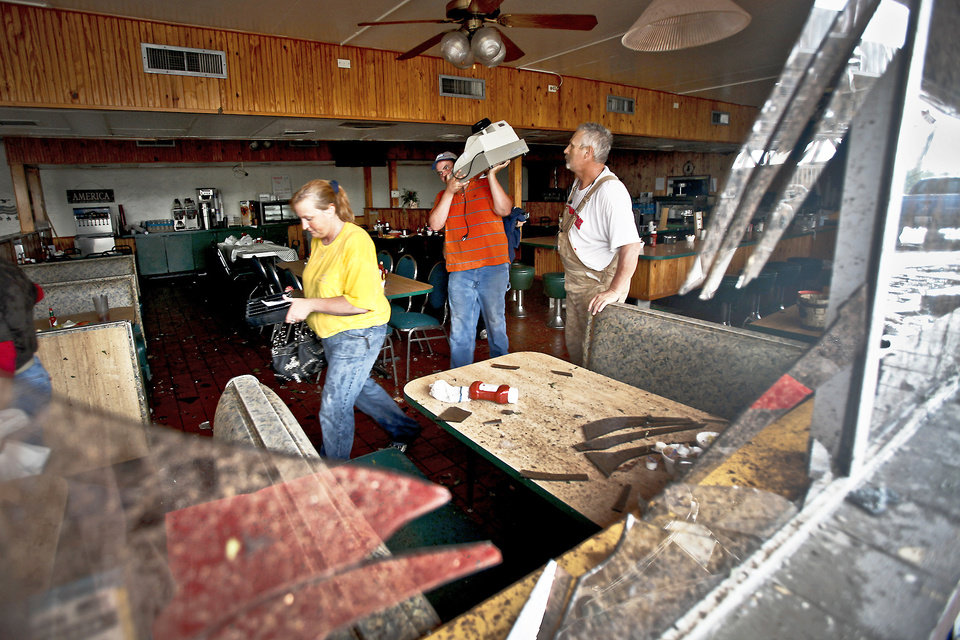 Photo - Seen through a broken window, employees gather valuables from the inside of the Anderson Travel Plaza after a tornado damaged the area Monday around Interstate 40 and Choctaw Road in Oklahoma City. Photo by Chris Landsberger, The Oklahoman