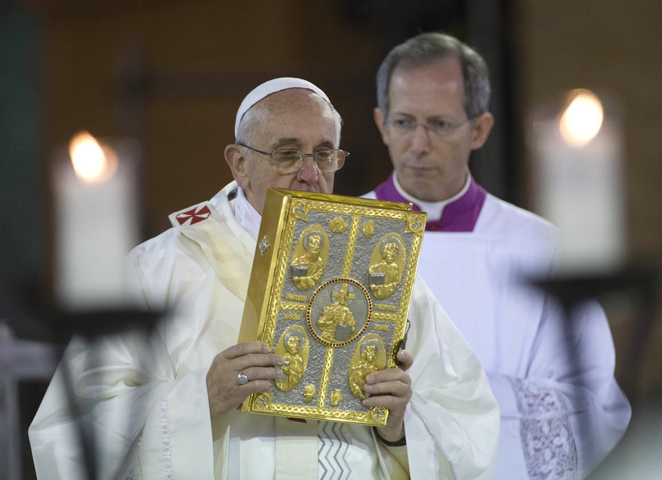 Photo - Pope Francis kisses the book of Gospels as Vatican Master of ceremonies Guido Marini stands behind him during Mass inside the Aparecida Basilica in Aparecida, Brazil, Wednesday, July 24, 2013. Pope Francis is on the third day of his trip to Brazil where he will attend the 2013 World Youth Day in Rio. (AP Photo/Domenico Stinellis)