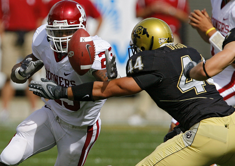Photo - Oklahoma's Allen Patrick (23) reaches out to grab his fumble in front of Colorado's Jordon Dizon (44) during the first half of the college football game between the University of Oklahoma Sooners (OU) and the University of Colorado Buffaloes (CU) at Folsom Field on Saturday, Sept. 29, 2007, in Boulder, Co.   By CHRIS LANDSBERGER, The Oklahoman  ORG XMIT: KOD