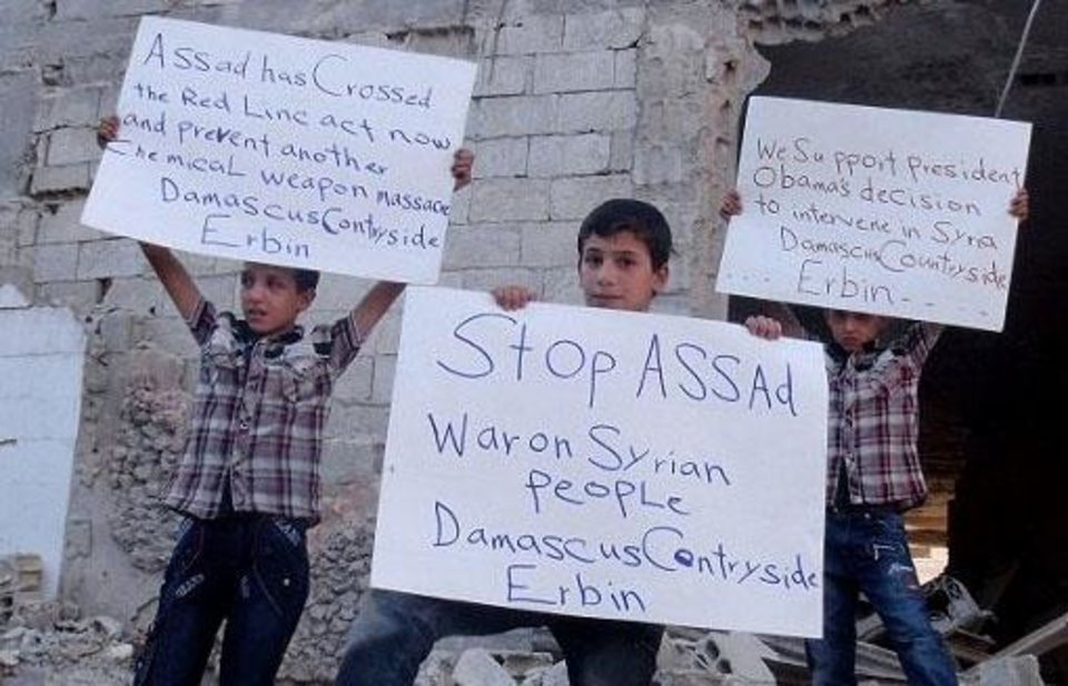 Photo - In this citizen journalism image provided by the United media office of Arbeen which has been authenticated based on its contents and other AP reporting, Syrian children hold posters as the pose for a photograph in Arbeen town, a suburb of Damascus, Syria, Tuesday, Sept. 3, 2013. (AP Photo/United media office of Arbeen)