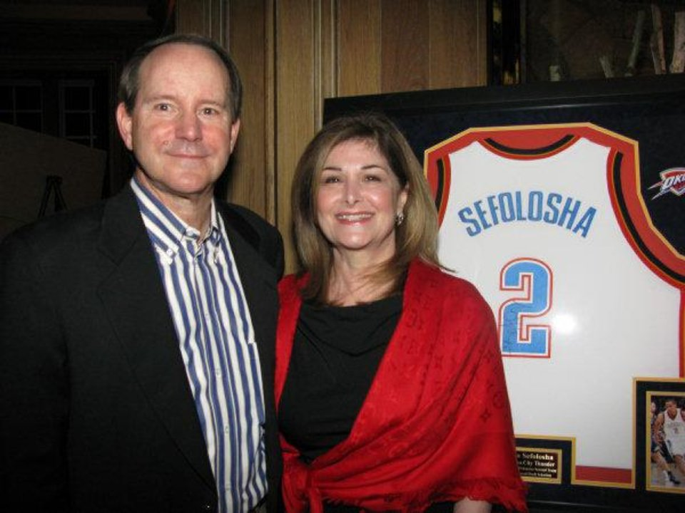 Photo - Bill and Donna Bozalis stand in front of Thabo Sefolosha's autographed jersey donated to an auction to raise money for a youth sports program in South Africa. Photo by Lillie-Beth Brinkman, The Oklahoman.