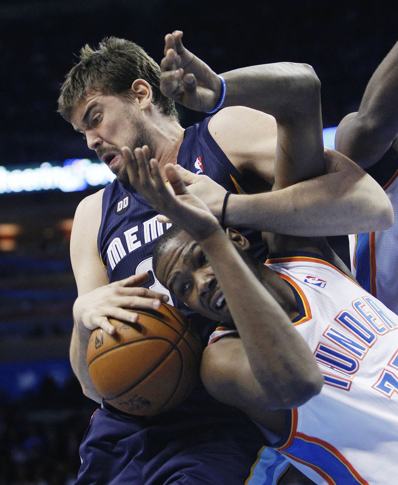 Memphis Grizzlies center Marc Gasol, left, wraps up Oklahoma City Thunder forward Kevin Durant, right, as he grabs a rebound in the second quarter of an NBA basketball game in Oklahoma City, Wednesday, Nov. 14, 2012. (AP Photo/Sue Ogrocki)