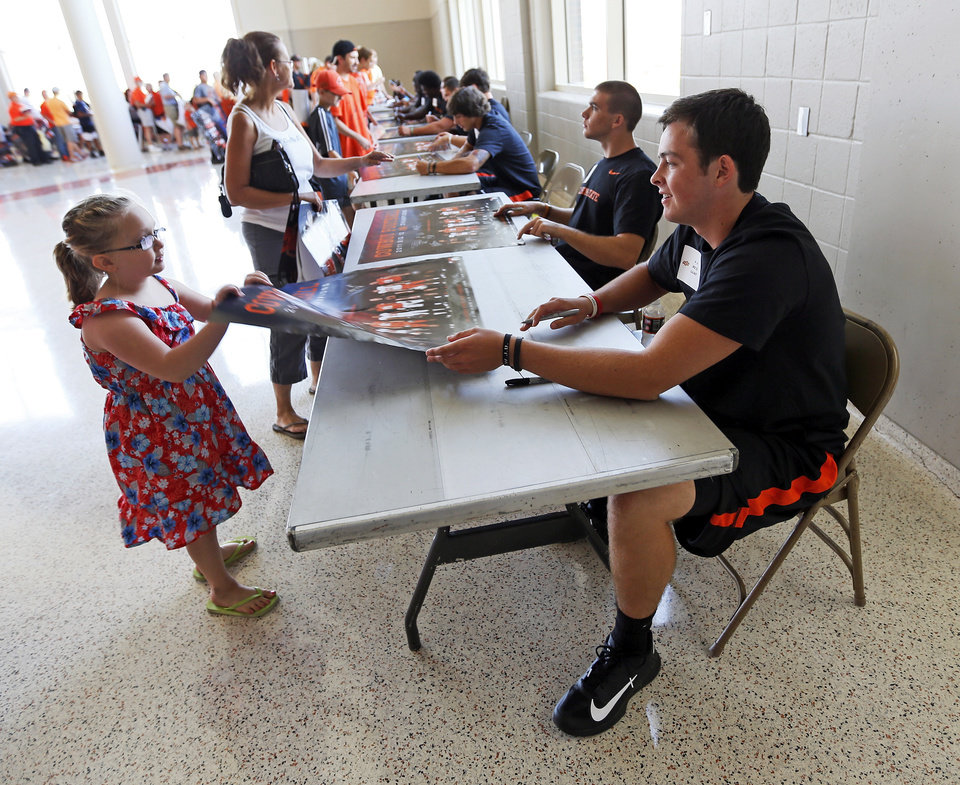 Oklahoma State quarterback Wes Lunt, right, hands a poster to fan Emma Shideler, 6, of Drumright, after signing an autograph during OSU Fan Appreciation Day at Gallagher-Iba Arena in Stillwater, Okla., Saturday, Aug. 4, 2012. Photo by Nate Billings, The Oklahoman