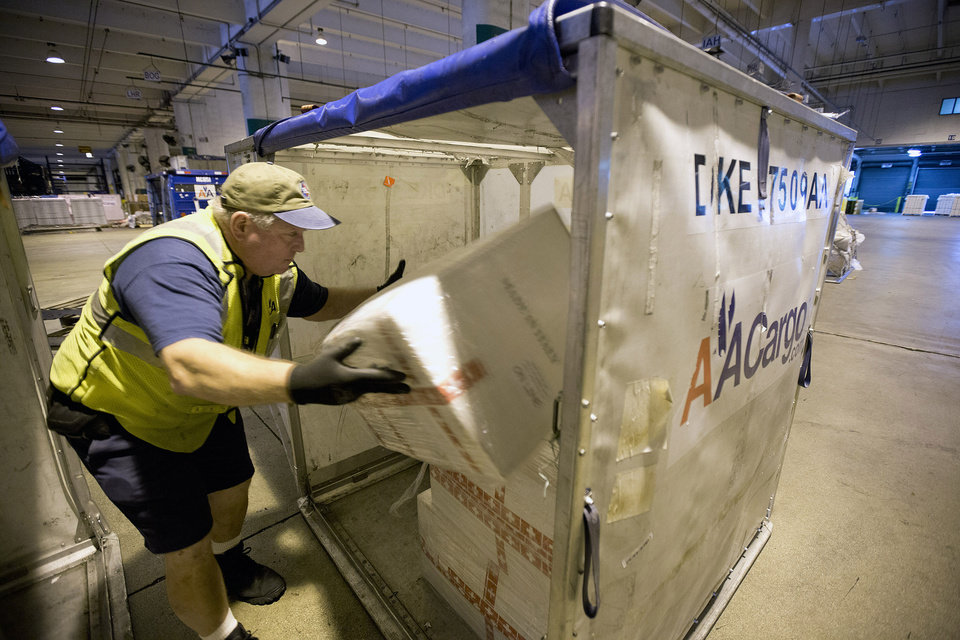 Photo - In this Jan. 9, 2014 photo, Andy Hines,  an American Airlines worker,  loads cargo into a container at the Miami airport, for shipment, in Miami. In the weeks leading up to Valentine's Day, about 738 million flowers come through the airport. (AP Photo/J Pat Carter)