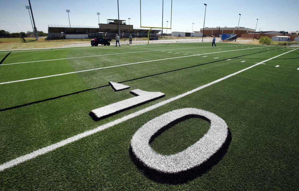 Photo - Above and below: Workers install artificial turf on the practice field for Moore High School.  Photos by Steve Sisney, The Oklahoman
