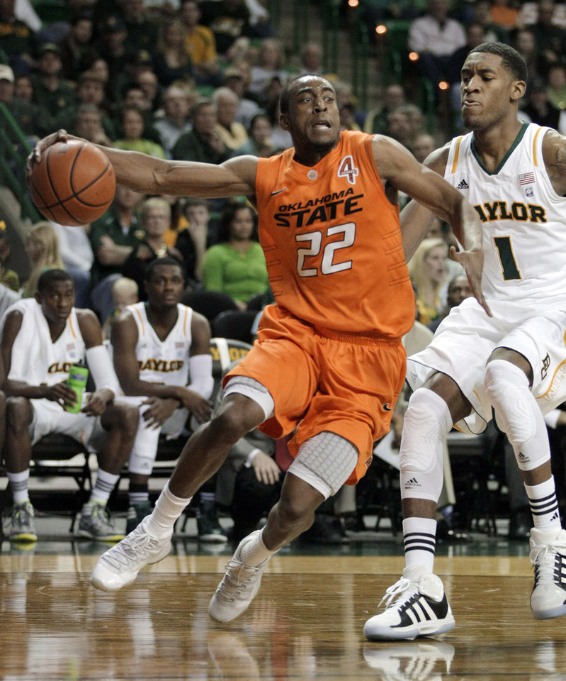 Oklahoma State guard Markel Brown (22) drives around Baylor forward Perry Jones III (1) to the basket in the first half of an NCAA college basketball game Saturday, Jan. 14, 2012, in Waco, Texas. (AP Photo/Tony Gutierrez) ORG XMIT: TXTG101