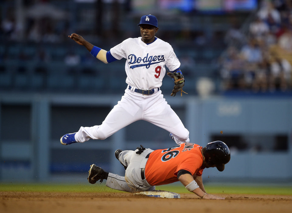 Photo - Miami Marlins' Garrett Jones, below, is forced out at second as Los Angeles Dodgers second baseman Dee Gordon attempts to throw out Marcell Ozuna at first during the second inning of a baseball game, Monday, May 12, 2014, in Los Angeles. Ozuna was safe at first on the play. (AP Photo)