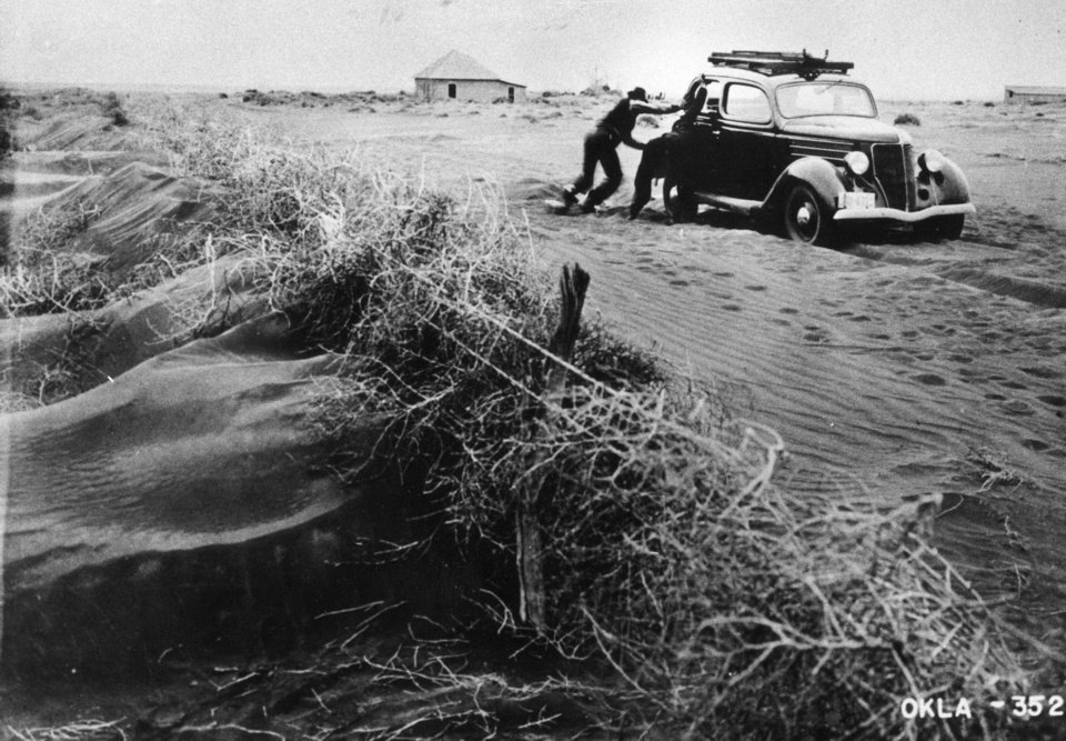 A motorist pushes his automobile, struggling to cross the dunes in Cimarron County in 1939. THE OKLAHOMAN ARCHIVES