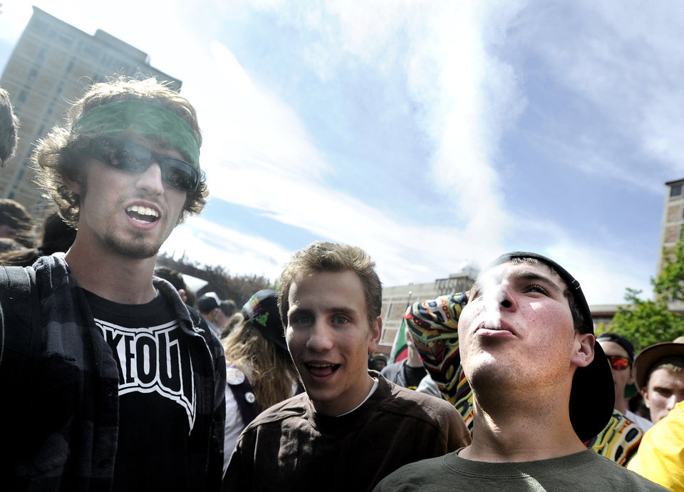 Photo -   An unidentified man, at right, exhales a plume of smoke after smoking a marijuana cigarette in the crowd of marijuana supporters outside of the Duane Physics building during the 4/20 rally on the University of Colorado campus in Boulder, Colo., on Friday, April 20, 2012. Many students at the University of Colorado and other campuses across the country have long observed 4/20. The counterculture observation is shared by marijuana users from San Francisco's Golden Gate Park to New York's Greenwich Village. (AP Photo/The Daily Camera, Jeremy Papasso)