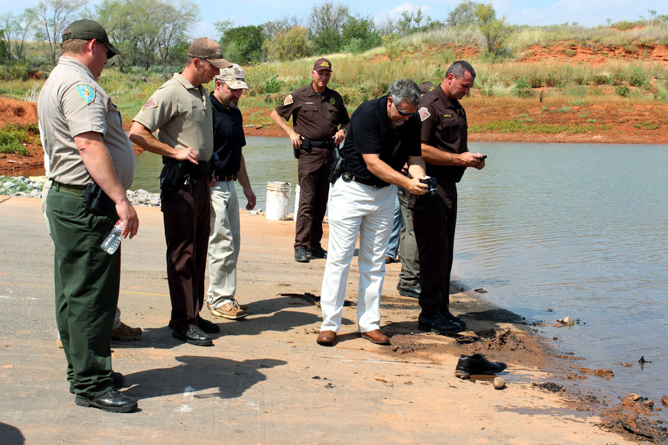 In this Sept. 17, 2013, photo, officials investigate the scene at Foss Lake, Okla. where two decades-old cars were pulled from the water by a dive team. The Oklahoma State Medical ExaminerÂ's Office says authorities have recovered skeletal remains of multiple bodies in the Oklahoma lake where the cars were recovered. (AP Photo/The Elk City Daily News, Larissa Graham) ORG XMIT: TXKJ103