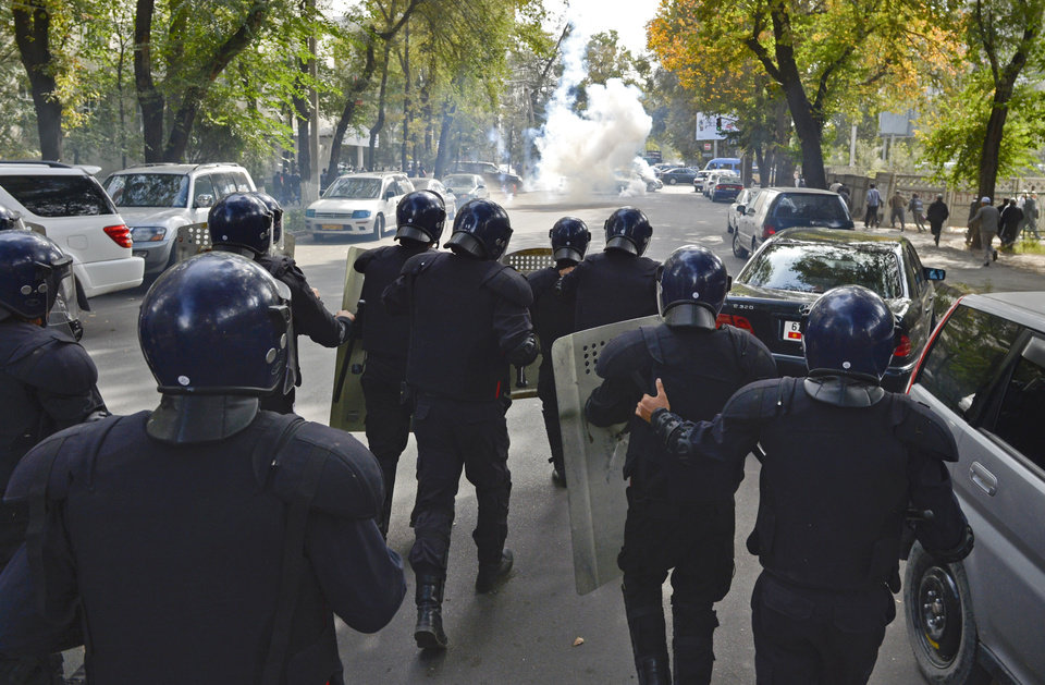 Photo -   Police officers use tear gas trying to stop protesters in downtown Bishkek, Kyrgyz capital on Wednesday, Oct. 3, 2012. Around 1,000 people gathered in the center of the city for a rally, organized by nationalist politicians Sapar Zhaparov and Kamchibek Tashiyev, ostensibly to demand the nationalization of a controversial gold mine in the east of the Central Asian nation. Police officers protecting the government building, known as the White House, used dogs and smoke bombs to disperse a group of young men who attempted to scale the gates. (AP Photo/ Vladimir Voronin)
