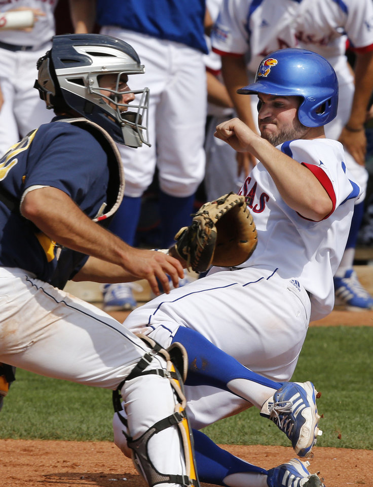 Photo - Kansas' Dakota Smith, right, begins his slide past West Virginia catcher Cameron O'Brien, left, in the fifth inning of a first-round game in the Big 12 conference baseball tournament in Oklahoma City, Wednesday, May 21, 2014. Smith was safe on the play on a double hit by Tucker Tharp. (AP Photo/Sue Ogrocki)