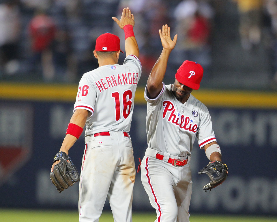 Photo - Philadelphia Phillies third baseman Cesar Hernandez (16) celebrates the win with shortstop Jimmy Rollins (11) in a baseball game against the Atlanta Braves Tuesday, June 17, 2014, in Atlanta. The Phillies won 5-2. (AP Photo/Todd Kirkland)
