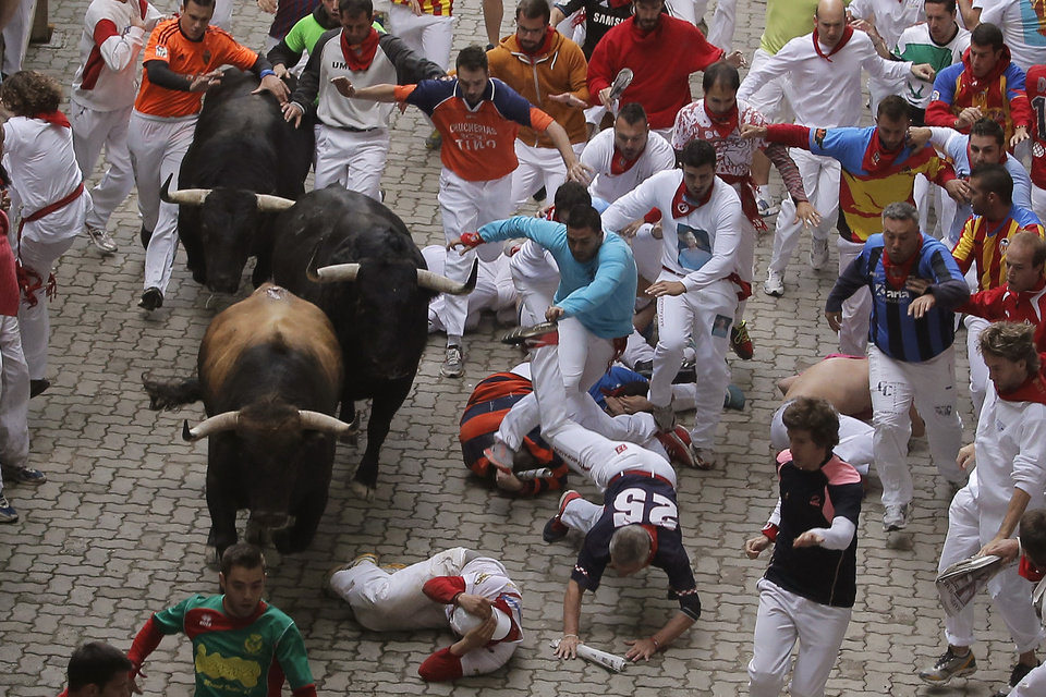 Photo - Revelers fall as Garcigrande fighting bulls run during the running of the bulls at the San Fermin festival, in Pamplona, Spain, Thursday, July 10, 2014. Revelers from around the world arrive to Pamplona every year to take part in some of the eight days of the running of the bulls. (AP Photo/Andres Kudacki)